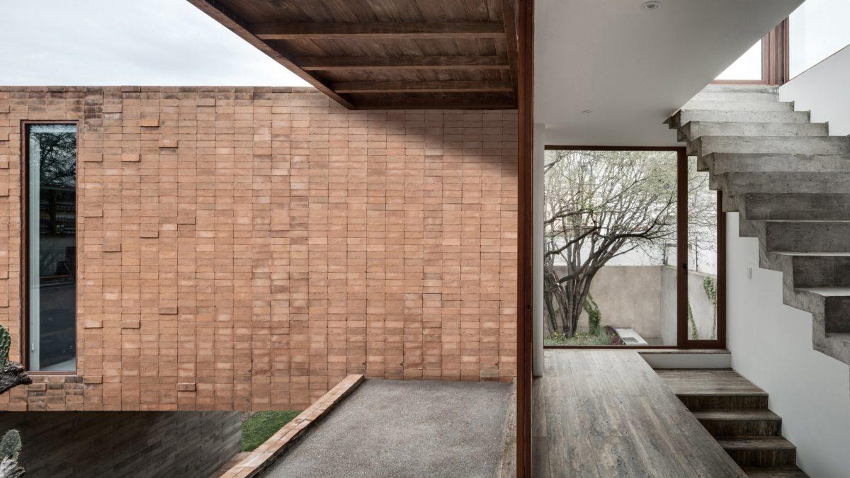 Casa in mattoni di argilla e cemento che circonda un albero di cactus_Messico_AS/D Asociación de Diseño